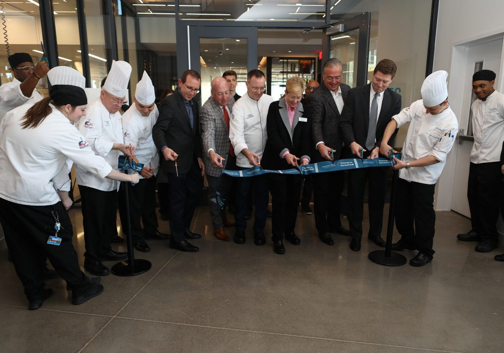 Chefs and staff cutting a blue ribbon at the Columbus State ribbon cutting ceremony.