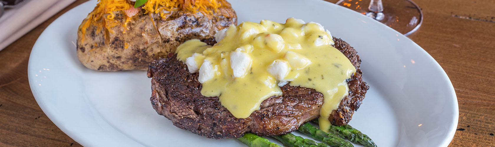 Steak dish with a loaded baked potato and asparagus on the side