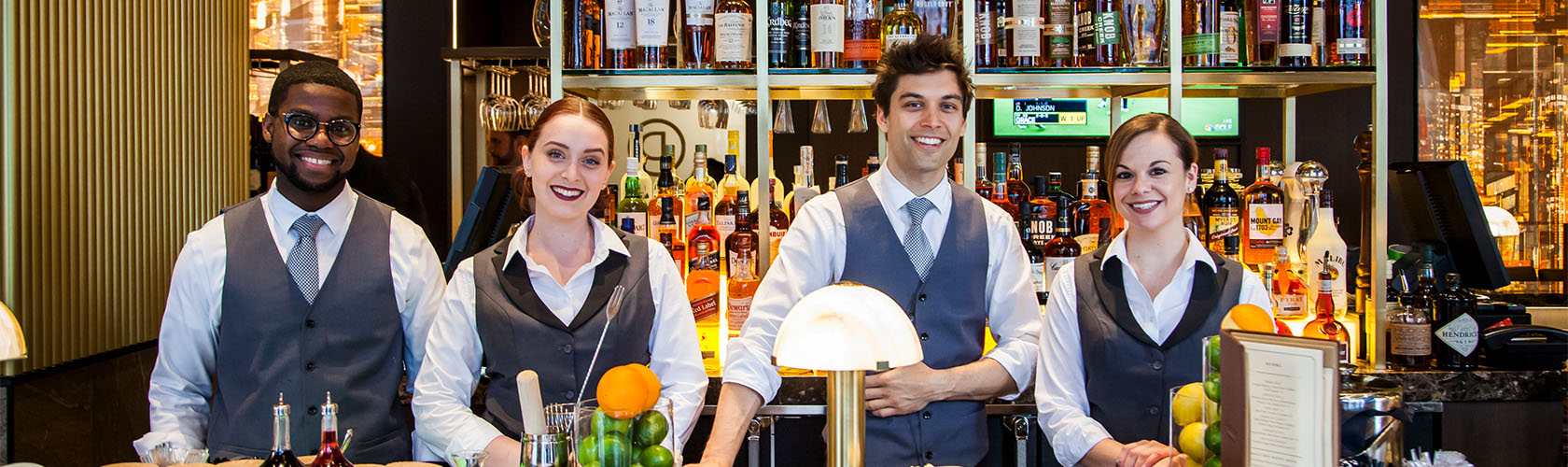 Ocean Prime bartenders behind the bar, smiling for the photo