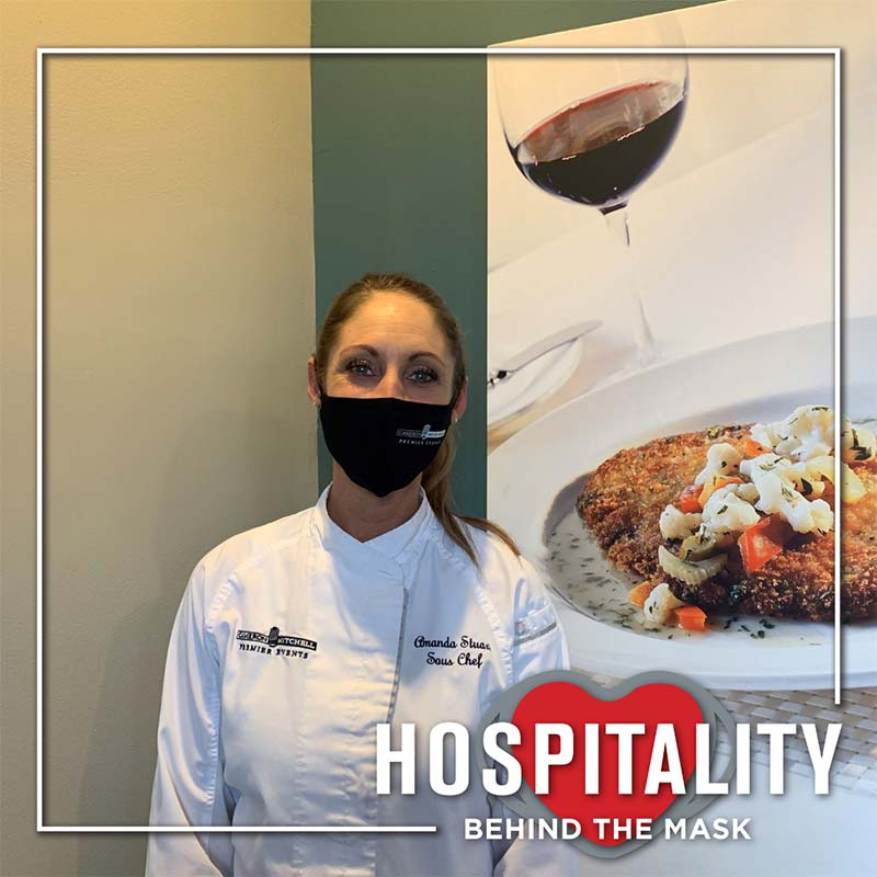Hospitality worker in white chef coat with safety mask.