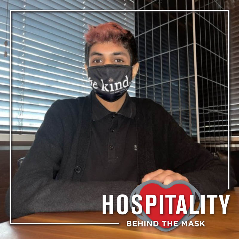 Hospitality worker in restaurant with safety mask.