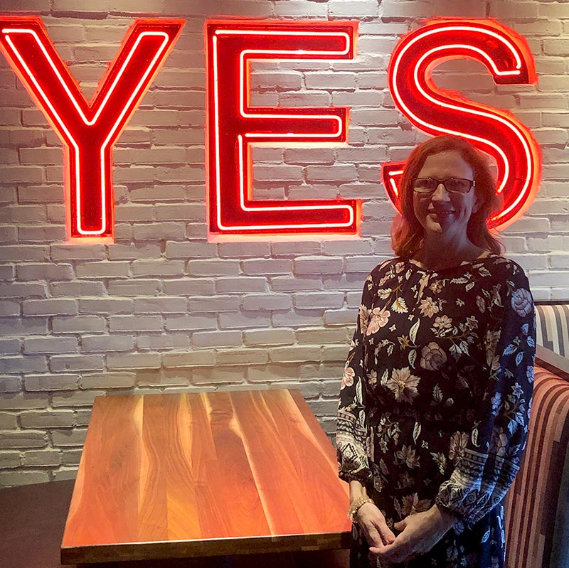 Caroline Brown standing in front of the neon 'YES' sign at Cameron Mitchell Restaurants' headquarters.
