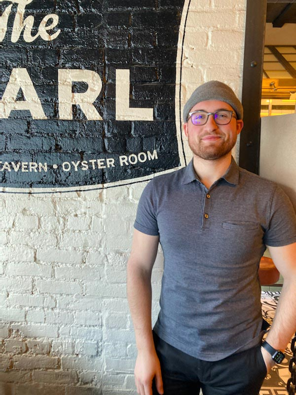 Marcus King standing next to the painted Pearl sign inside the restaurant.